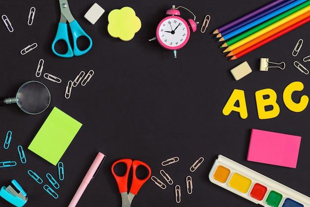 Al centro dello sfondo scuro è presente uno spazio vuoto per testo o iscrizioni. ci sono materiale scolastico e scolastico in giro. immagini in alto, mock up.