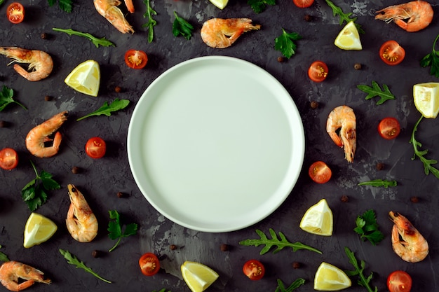Al centro di uno sfondo scuro strutturato un piatto grigio vuoto