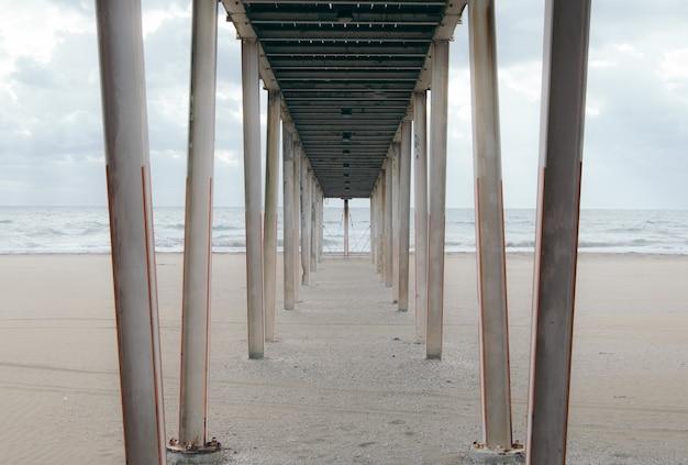 Al di sotto di un molo di legno sulla spiaggia di sabbia in una giornata nuvolosa