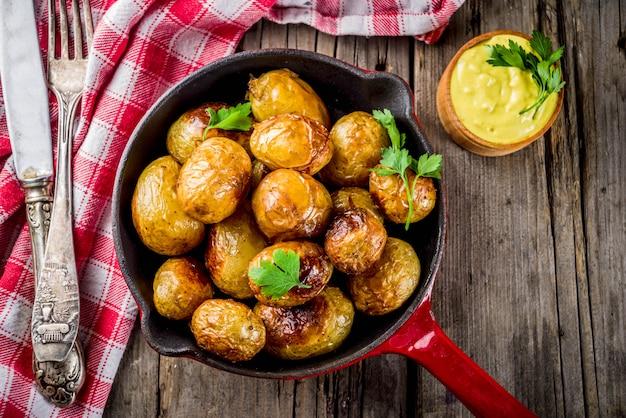 Al forno in padella patate intere giovani, cibo vegetariano fatto in casa, vecchio tavolo rustico in legno, con salsa, copia spazio