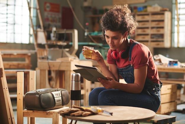 Al laboratorio di falegnameria. giovane falegname femmina graziosa in denim globale che riposa sulla panca di legno con una tazza di tè e un libro di lettura sulla tavoletta digitale