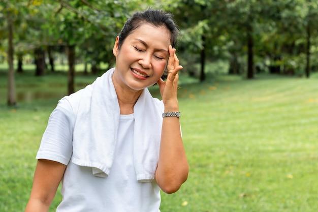 Al mattino donna anziana mal di testa asiatico durante l'esercizio al parco.