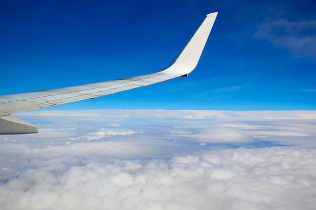 Ala dell'ala che vola in cielo blu e nuvole