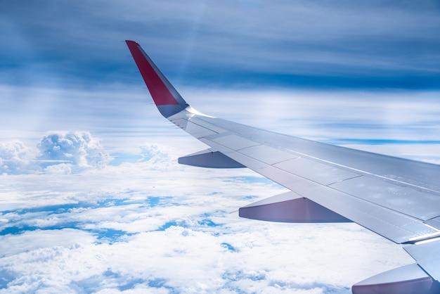 Ala di un aereo su cielo blu con nuvole vista attraverso la finestra.