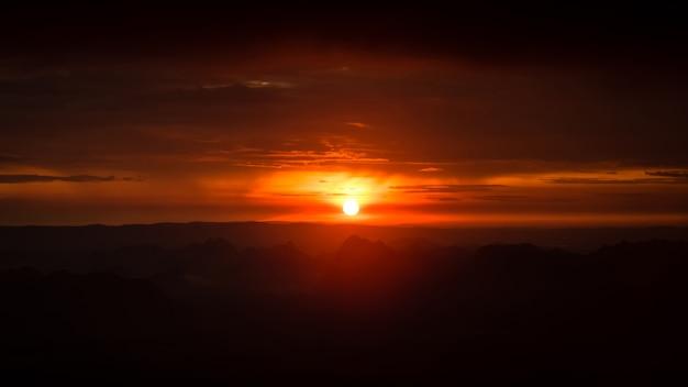 Alba al mattino, che galleggia sulle vaste montagne. i colori del cielo sono rossi e
