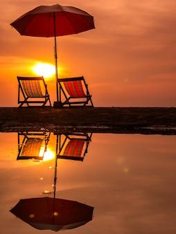 Alba con cielo arancione mattina con sedia e ombrellone sulla spiaggia di riflessione in acqua