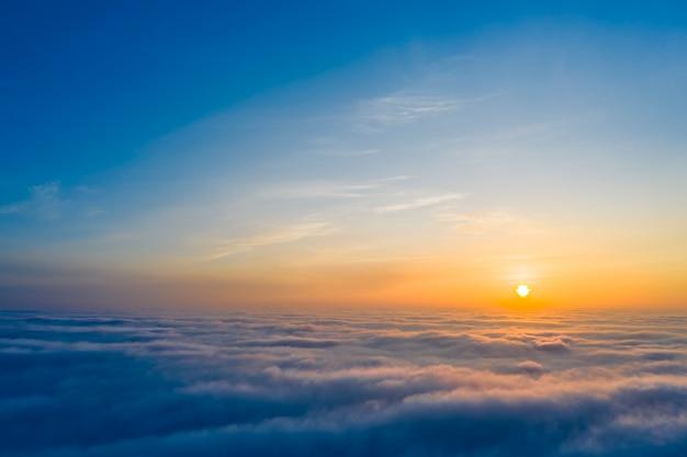 Alba gialla e blu sopra le nuvole, il concetto, il viaggio e lo svago.