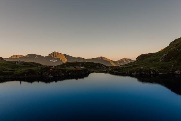 Alba, in vista del lago di capra, tende nei carpazi, fagaras, romania, all'aperto