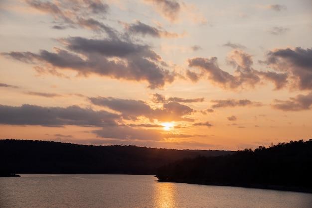 Alba naturale di tramonto sopra il campo con la montagna