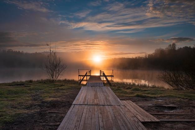 Alba su un lago nebbioso con un molo in legno nella foresta al mattino presto
