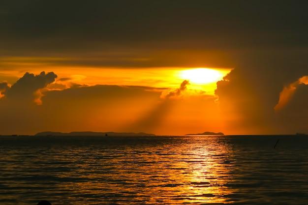 Alba sulla barca di pesca del cielo della nuvola della siluetta e sull'isola del mare