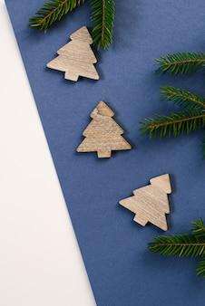 Alberi di natale e rami di albero di legno delle decorazioni del nuovo anno o di natale su fondo blu con lo spazio della copia per testo. concetto di natale, festa, festa e celebrazione per cartolina o invito