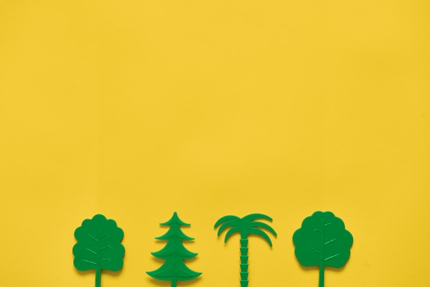 Alberi verdi su giallo. ecologia della natura piatta. copyspace