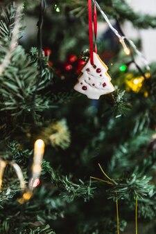 Albero bianco di pan di zenzero di natale dipinto a mano sull'albero di natale. avvicinamento.