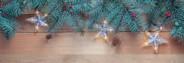 Albero di abete di natale e ghirlanda sul tavolo di legno, banner