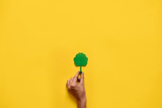 Albero di legno del giocattolo di plastica su giallo. minimo ambiente di ecologia piatta
