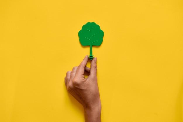 Albero di legno del giocattolo di plastica su giallo. minimo ambiente layecology piatto