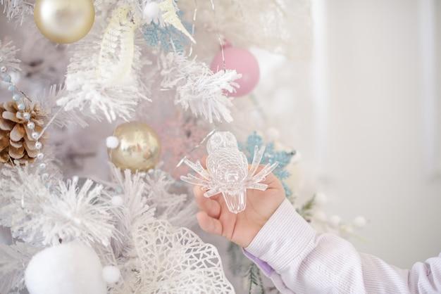 Albero di natale bianco. albero e decorazione del nuovo anno e mano dei ragazzi.