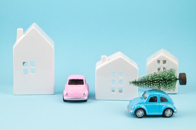 Albero di natale carring della piccola automobile del giocattolo sopra il tetto. feste sesonal, biglietto di auguri