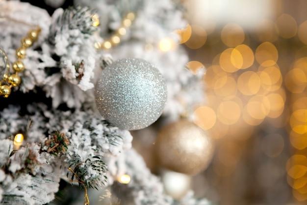 Albero di natale con giocattoli e neve decorativa per un felice anno nuovo