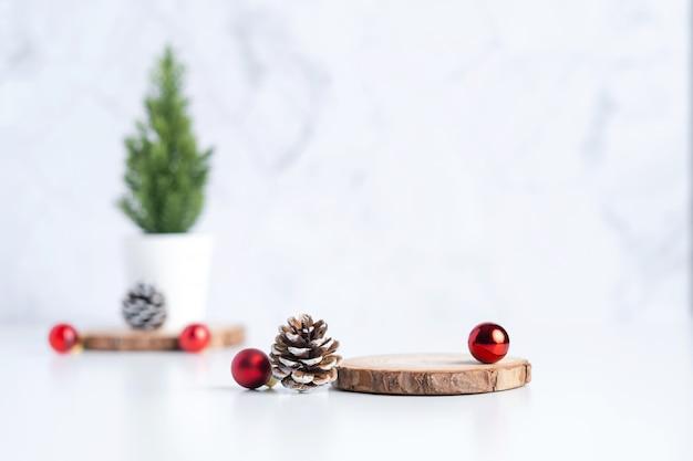 Albero di natale con la palla di natale della decorazione e della pigna e piatto di ceppo di legno vuoto sulla tavola e sul marmo