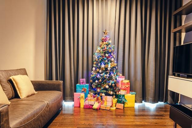 Albero di natale con luci e molti contenitori di regalo in salotto