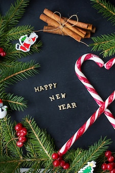 Albero di natale con ornamenti e caramelle su sfondo nero. l'iscrizione felice anno nuovo