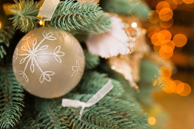 Albero di natale con palla d'oro con fiocco di neve. tema di felice anno nuovo