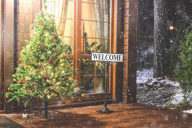 Albero di natale con scritta di benvenuto all'esterno.