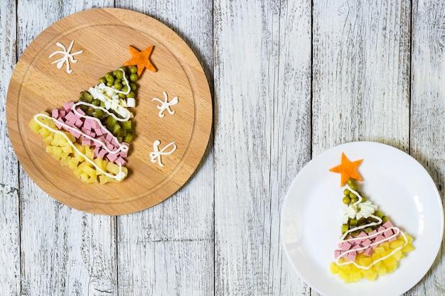 Albero di natale da un'insalata olivier nel piatto su un tavolo di legno bianco,