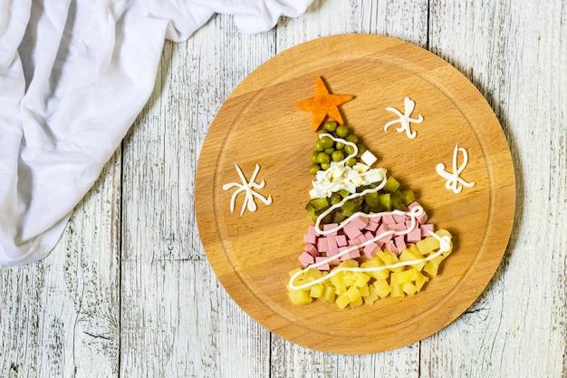 Albero di natale da un'insalata olivier sul tagliere su un tavolo di legno bianco,