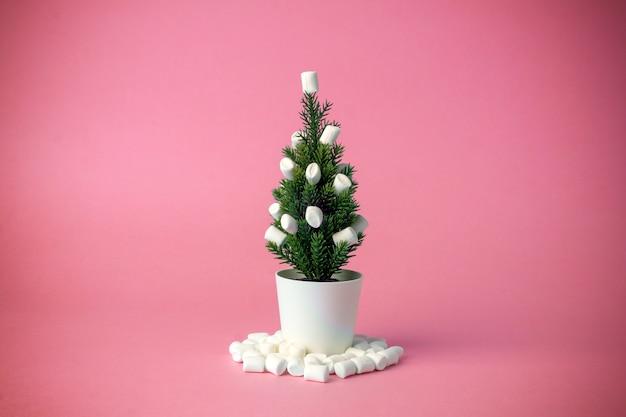 Albero di natale decorato con marshmallow invece di giocattoli su uno sfondo rosa.