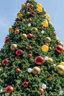 Albero di natale decorato con ornamenti rossi, gialli e argento con sfondo luminoso del cielo.