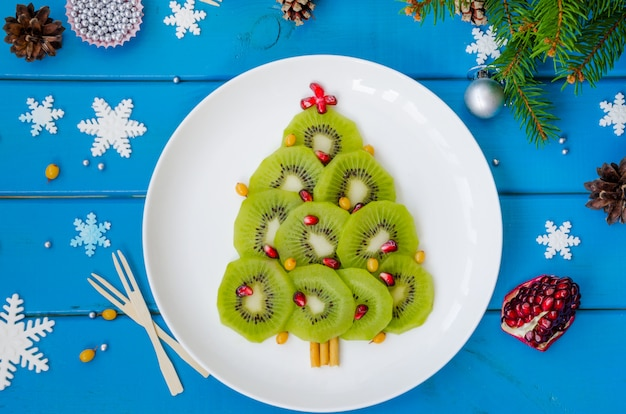 Albero di natale del kiwi su un piatto bianco con il melograno e l'olivello spinoso