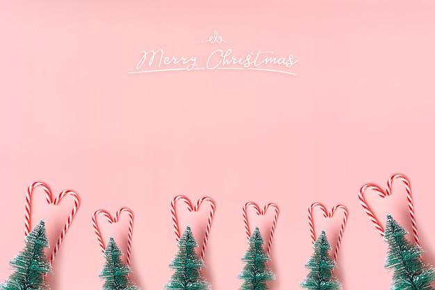 Albero di natale dell'albero con il bastoncino di zucchero che appende sulla parete di rosa pastello con buon natale bianco