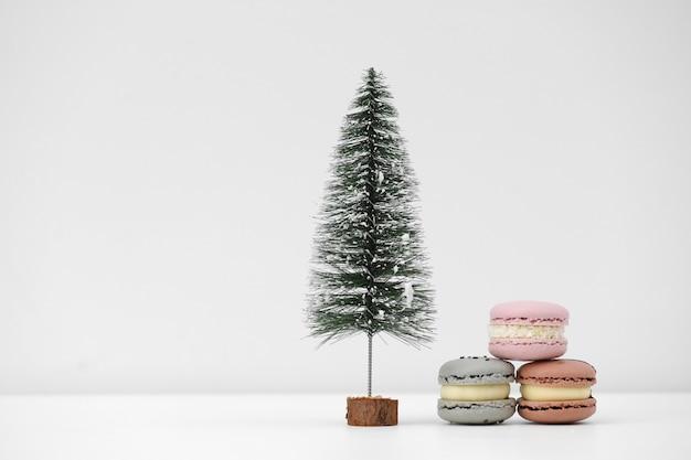 Albero di natale e maccheroni francesi o dessert dei macarons su una priorità bassa bianca. dolci sotto l'albero di natale