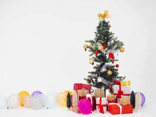 Albero di natale e scatola regalo con palloncino su sfondo bianco