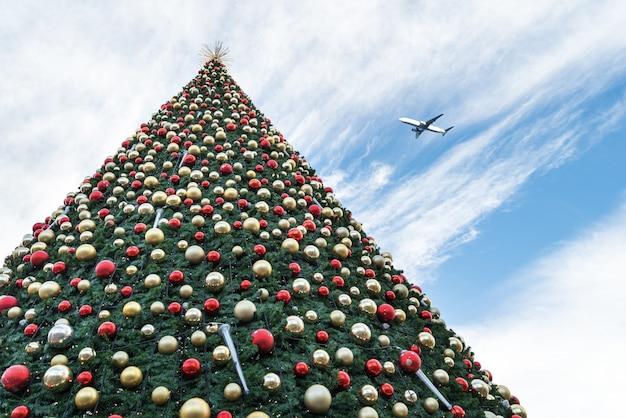 Albero di natale ed aeroplano decorati in cielo blu