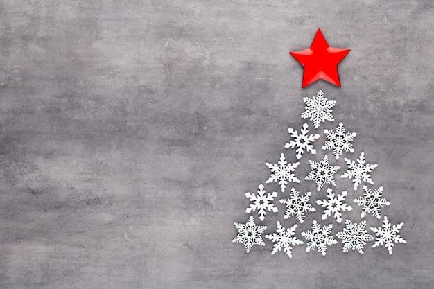 Albero di natale fatto da decorazioni di fiocchi di neve bianca su sfondo grigio con spazio vuoto copia per il testo. cartolina di natale e capodanno.