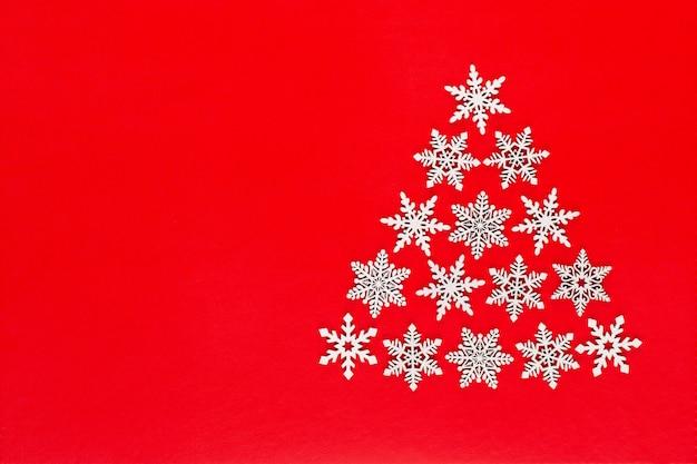 Albero di natale fatto dalle decorazioni bianche del fiocco della neve su fondo rosso con lo spazio vuoto della copia per testo. cartolina di natale e capodanno.