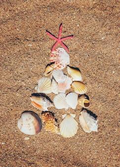 Albero di natale fatto di conchiglie nella sabbia
