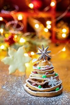 Albero di natale fatto di fette d'arancia essiccate e anice stellato, con luce festiva e biscotto
