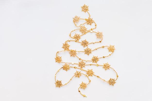 Albero di natale fatto di ghirlanda di fiocchi di neve d'oro.