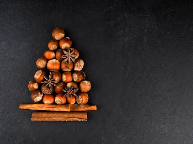 Albero di natale fatto di noci, spezie e arance secche su sfondo nero