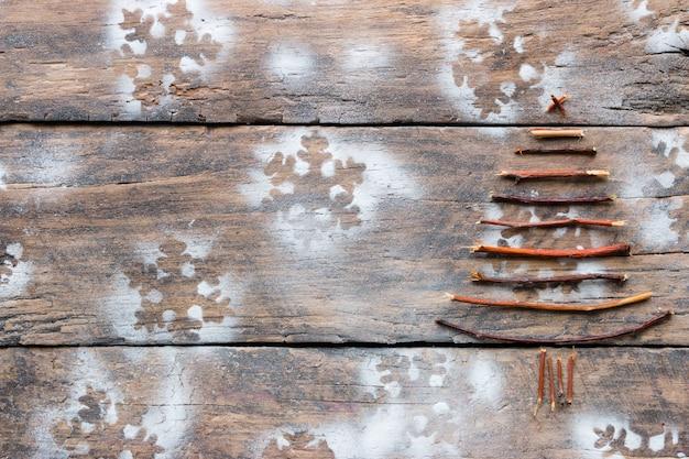Albero di natale fatto ramoscelli di legno con fiocchi di neve