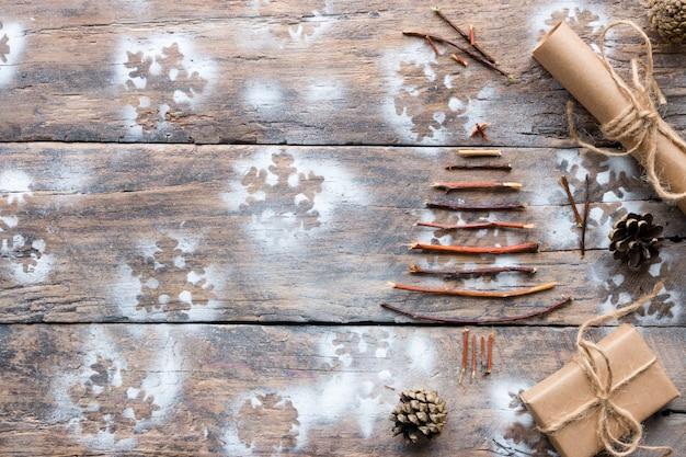 Albero di natale fatto ramoscelli, regali e coni sul legno