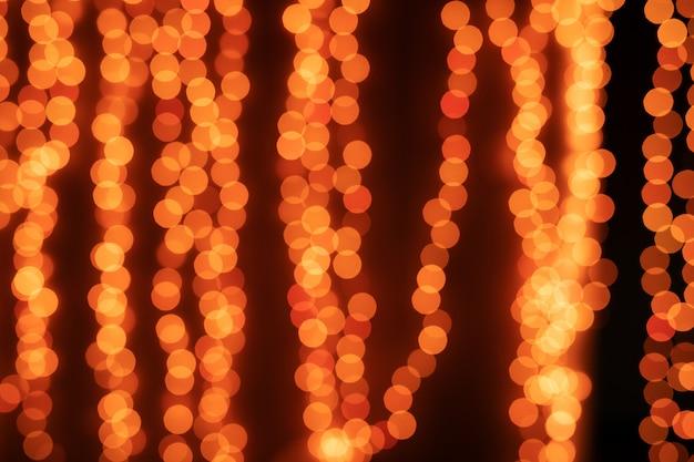 Albero di natale giallo bokeh sul nero delle luci scintillanti defocused