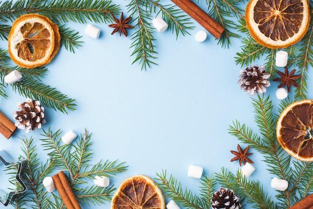 Albero di natale matto delle pigne delle spezie delle arance dell'alimento sul blu