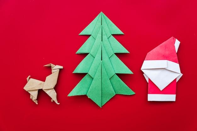 Albero di natale; renna; origami di carta babbo natale su sfondo rosso