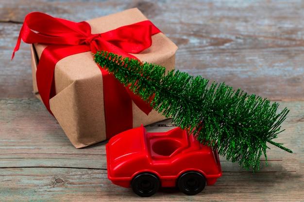 Albero di natale verde sull'automobile e sul regalo del giocattolo. concetto di celebrazione delle vacanze di natale
